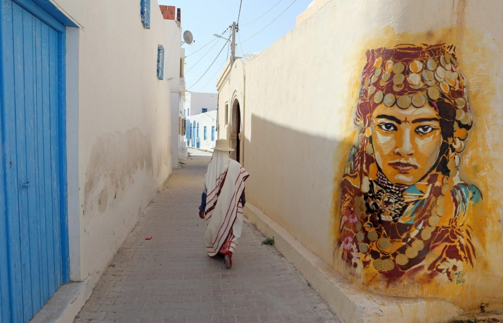 A Tunisian woman walks past a mural by Spanish artist Btoy. Photograph: Mohamed Messara/EPA