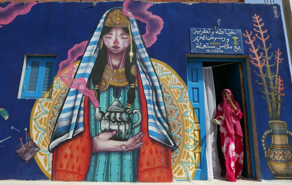 A seamstress stands at the entrance of her workshop decorated by Spanish artist Malakkai. Photograph: Mohamed Messara/EPA