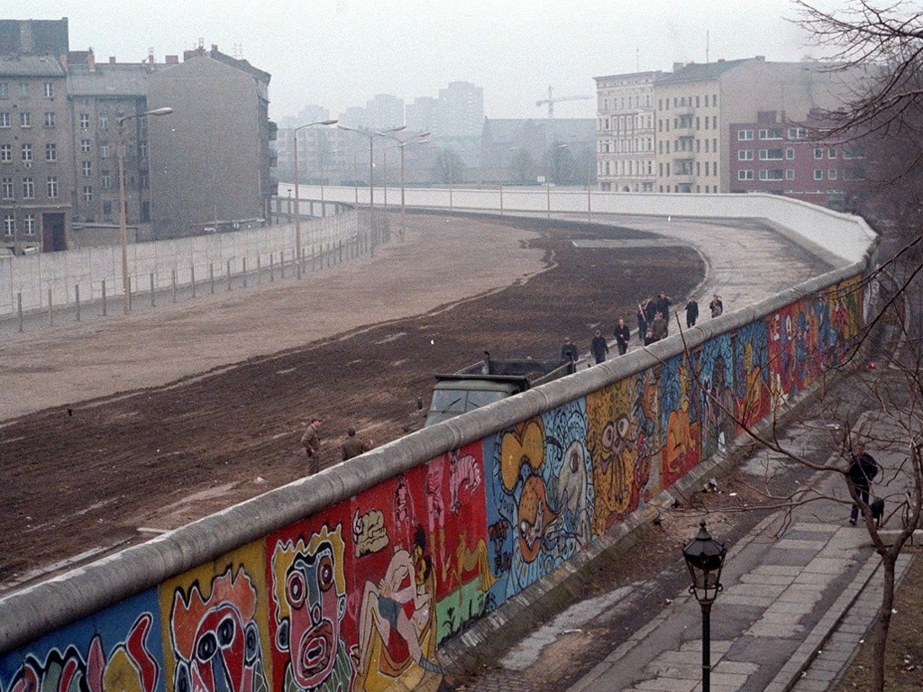 This was taken in 1986. You can see a GDR [East Germany] pioneer cleaning squad clearing away waste from West Berlin. In those days, people threw everything over the Wall. For some, it was a political act and people would scream 'Scheiss DDR' ('fuck the GDR') at the same time. I never threw anything over the Wall. It wasn't my style. Often, soldiers would come over with a megaphone to tell me to stop painting and to step back inside West Berlin. I would do so without any comment, but they would often try to catch me.