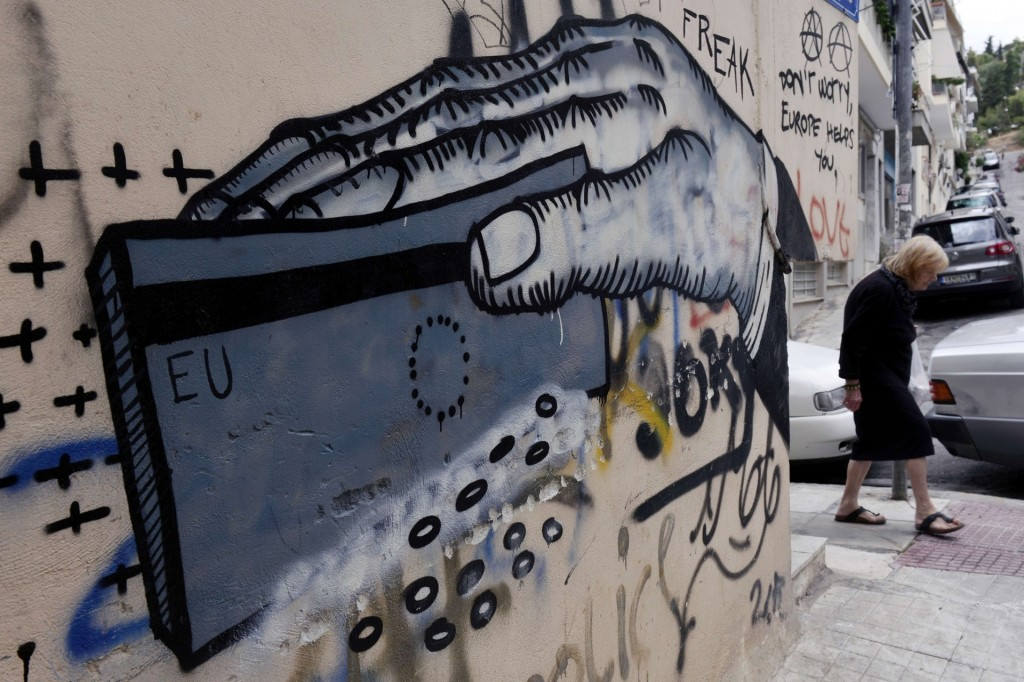 A woman passes graffiti in Athens Photograph: Louisa Gouliamaki/AFP/Getty