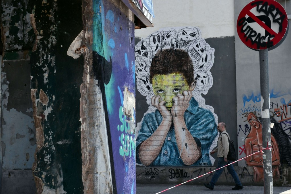 A child beset by demons, depicted on an abandoned building Photograph: Louisa Gouliamaki/AFP/Getty
