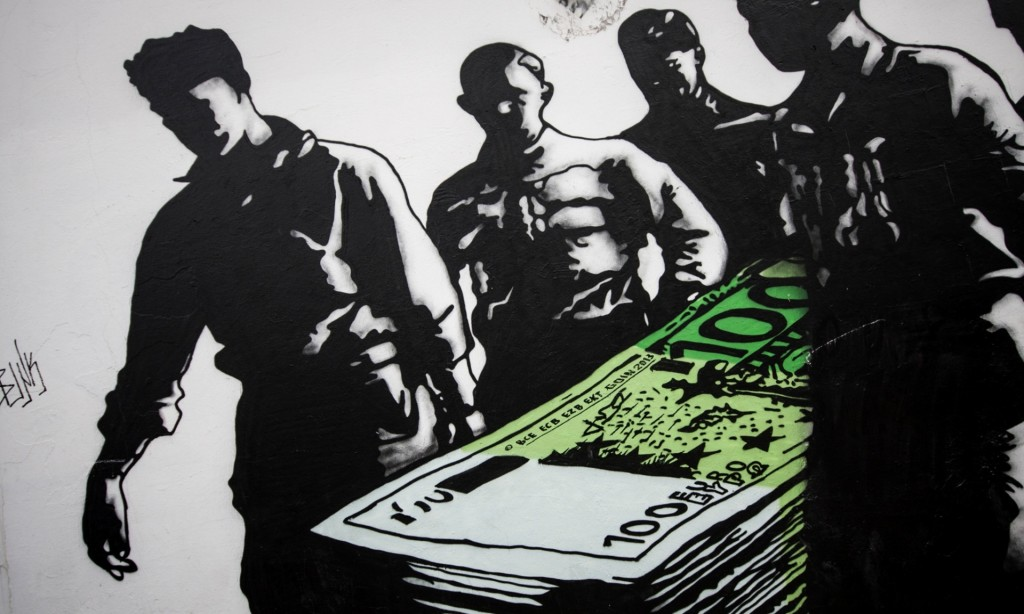 Street art in Athens shows a stack of euros depicted as a coffin. Photograph: Socrates Baltagiannis/dpa/Corbis