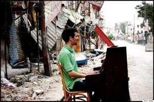 Ayham Ahmad plays in Yarmouk. (Photographer: Niraz Saied)